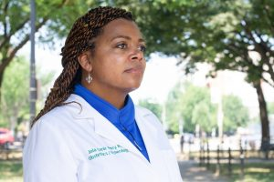 Headshot of Dr. Joia Crear-Perry, she is wearing a doctor's lab coat and looks thoughtful.