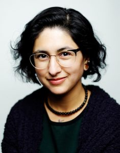 Headshot of Gabriela Zapata-Alma, a latino person, she is smiling and looking forward, she wears glasses and her hair is cut in a bob.